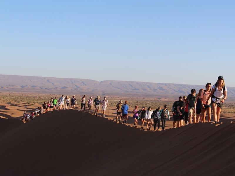 Group Walking Event Over Moroccan Sahara Sand Dunes