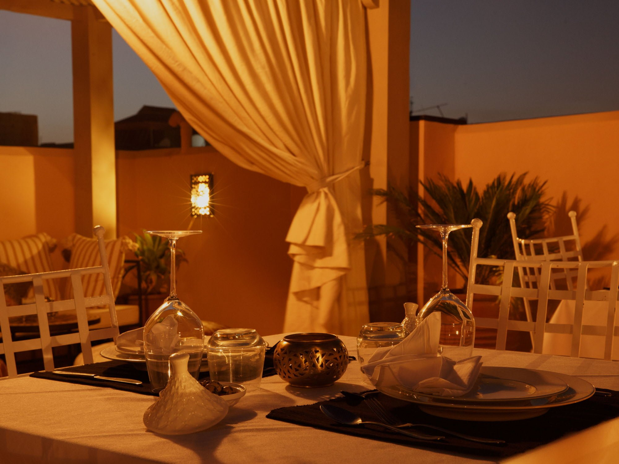 Laid Table at Riad Hotel Rooftop Garden with Wine Glasses, Plates, Napkins and Cutlery