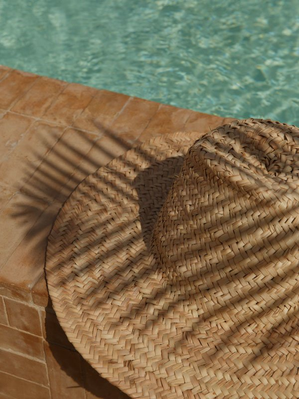 Straw Boater Hat Without Ribbon on Brick Wall of Swimming Pool