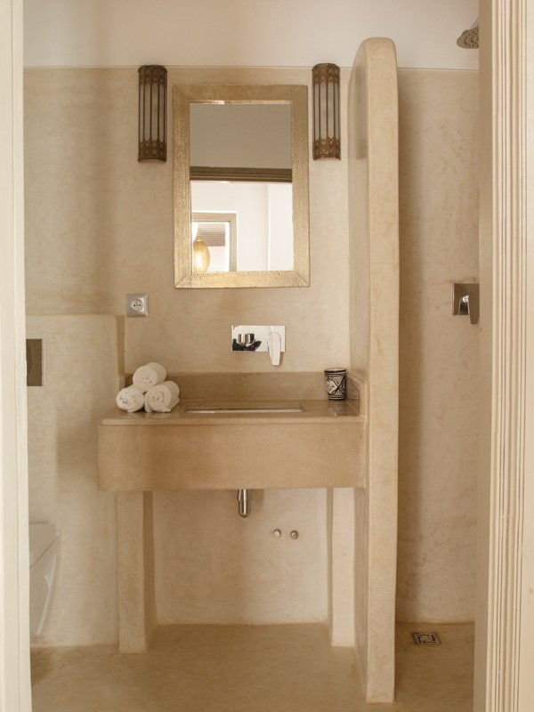 Luxury Marble Tiled Hotel Bathroom, with washbasin, shower, vanity mirror, courtesy towels and toiletries.