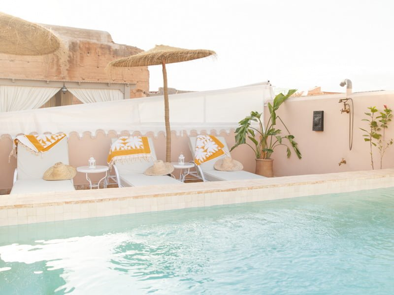 Straw Boater Hats and Towels on Shaded Sun Loungers next to Moroccan Hotel Pool