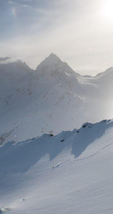 ENGADIN St.Moritz - Ein Freeskier zieht seine Spuren im Schneesportgebiet Corvatsch, Eiskristalle liegen in der Luft vor dem Piz Bernina (4049 m) mit Biancograt und dem Piz Roseg (3937 m).  A freeskier making tracks in the Corvatsch snow-sports area; ice crystals hang in the air against a backdrop of Piz Bernina (4049 m) with the Biancograt ridge and Piz Roseg (3937 m).  Un amante di free ski lascia le sue tracce nel comprensorio di sport invernali di Corvatsch, nella aria ci sono cristalli di ghiaccio sullo sfondo del Piz Bernina (4049 m) con il  Biancograt e il Piz Roseg (3937 m).  Copyright by ENGADIN St. Moritz By-line: swiss-image.ch/Romano Salis