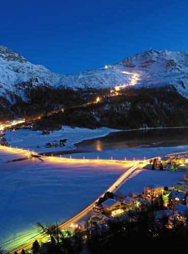 ENGADIN ST. MORITZ - Snownight auf dem Corvatsch - Blick von Silvaplana auf die laengste beleuchtete Skipiste (4.1 km) der Schweiz. Die beleuchtete Piste beginnt an der Mittelstation Corvatsch und geht ueber die Waldkerbe der Surlej-Piste zur Talstation, oberhalb des Ortes Surlej. Im Vordergrund die Lichter des Ortes Silvaplana.  Snow-night at Corvatsch - View from Silvaplana towards the longest illuminated ski slope of Switzerland (4.1 km). The illuminated slope begins at the middle station of Corvatsch and goes along the tree notch of the Surlej slope down to the station at the bottom which is just above the houses of Surlej. In the foreground the lights of the village of Silvaplana.  Snownight al Corvatsch - Vista da Silvaplana sulla piu lunga pista da sci illuminata della Svizzera (4.1 km). La pista illuminata comincia nella stazione intermedia del Corvatsch e va lungo il bosco della pista Surlej fino alla stazione nella valle al di sopra del paese di Surlej. In primo piano l'illuminazione di Silvaplana.  Copyright by ENGADIN St. Moritz By-line:swiss-image.ch/Robert Boesch