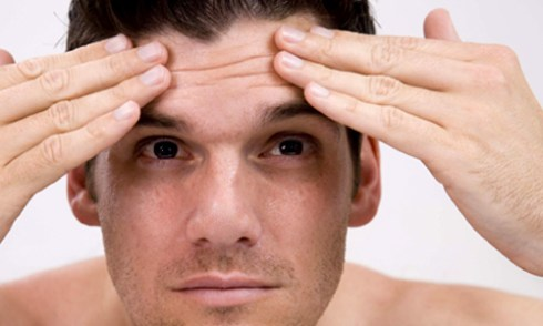 how to stop worrying man smoothing forehead wrinkles