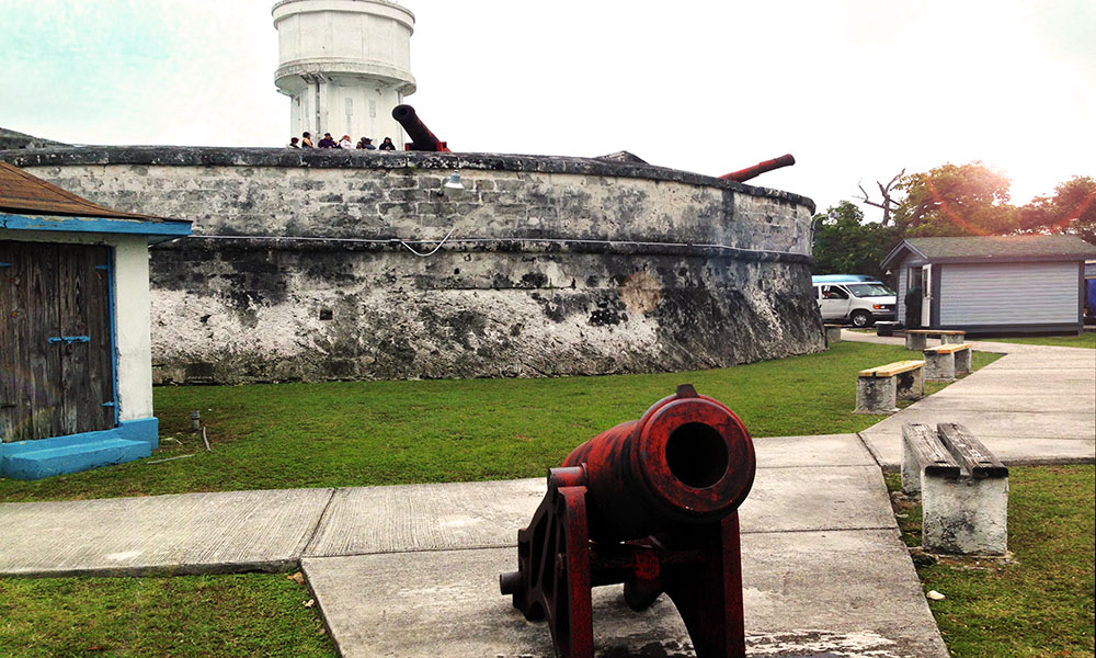 A bright red cannon beside the manicured lawns around Fort Fincastle, Nassau, Bahamas.