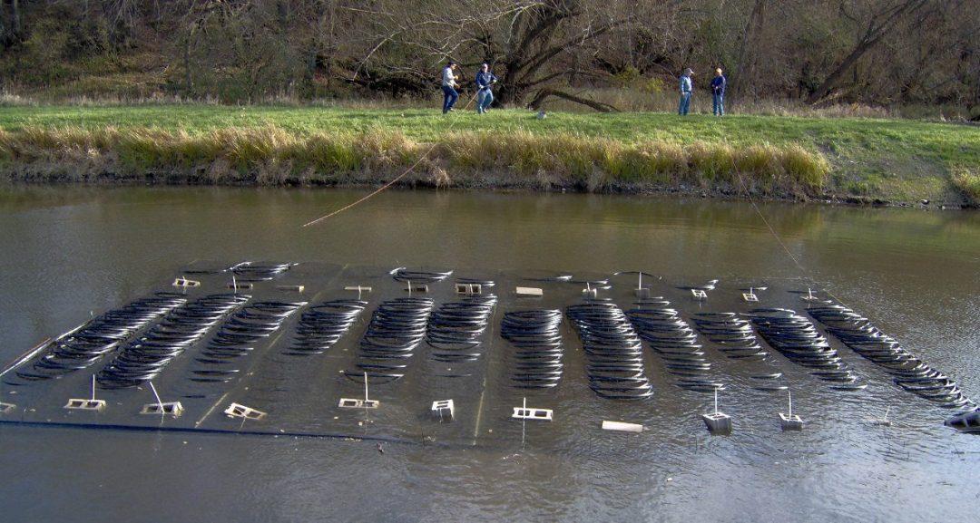 Water source heat pump coils being sunk in a pond