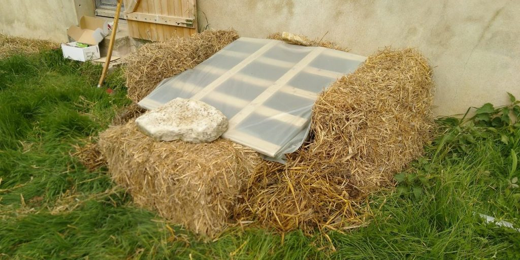A homemade straw bale mini-greenhouse
