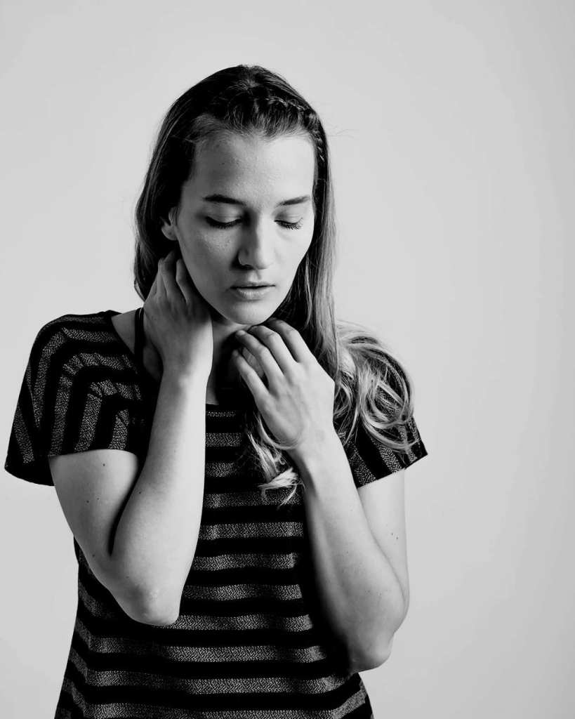 A black and white photograph of a woman wearing a stripey top with her hand to her throat as she looks down