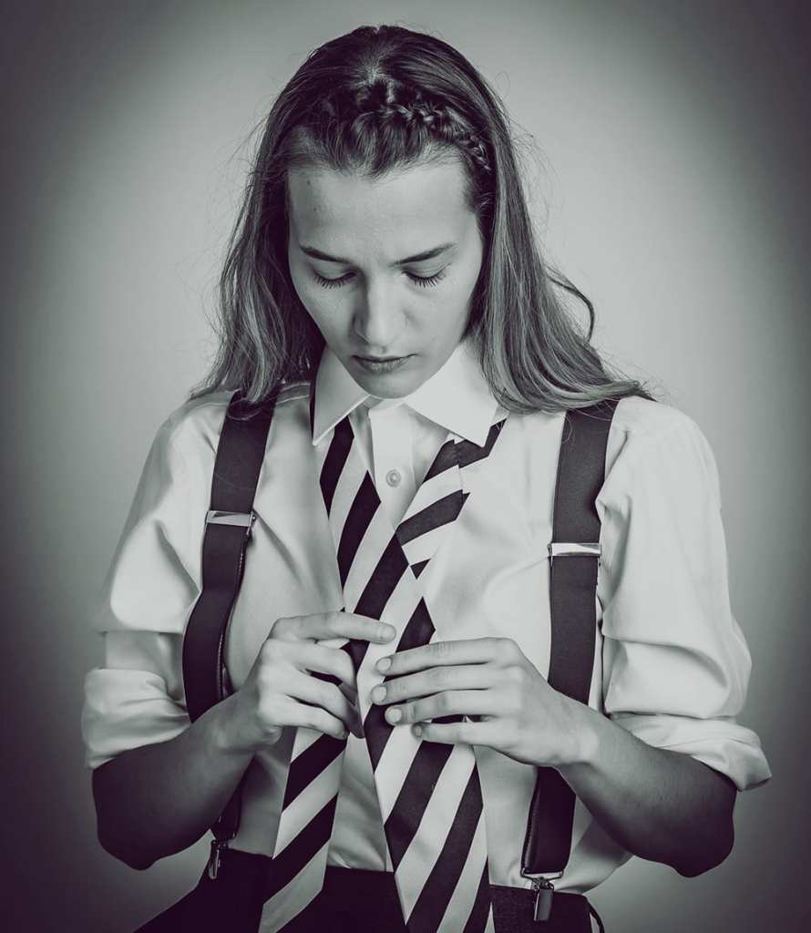 A black and white photograph of a woman wearing braces and tieing up a stripey tie