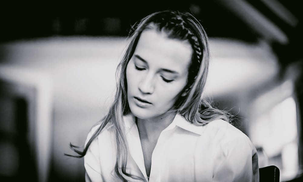A black and white photograph of a woman wearing a white shirt sitting in a kitchen