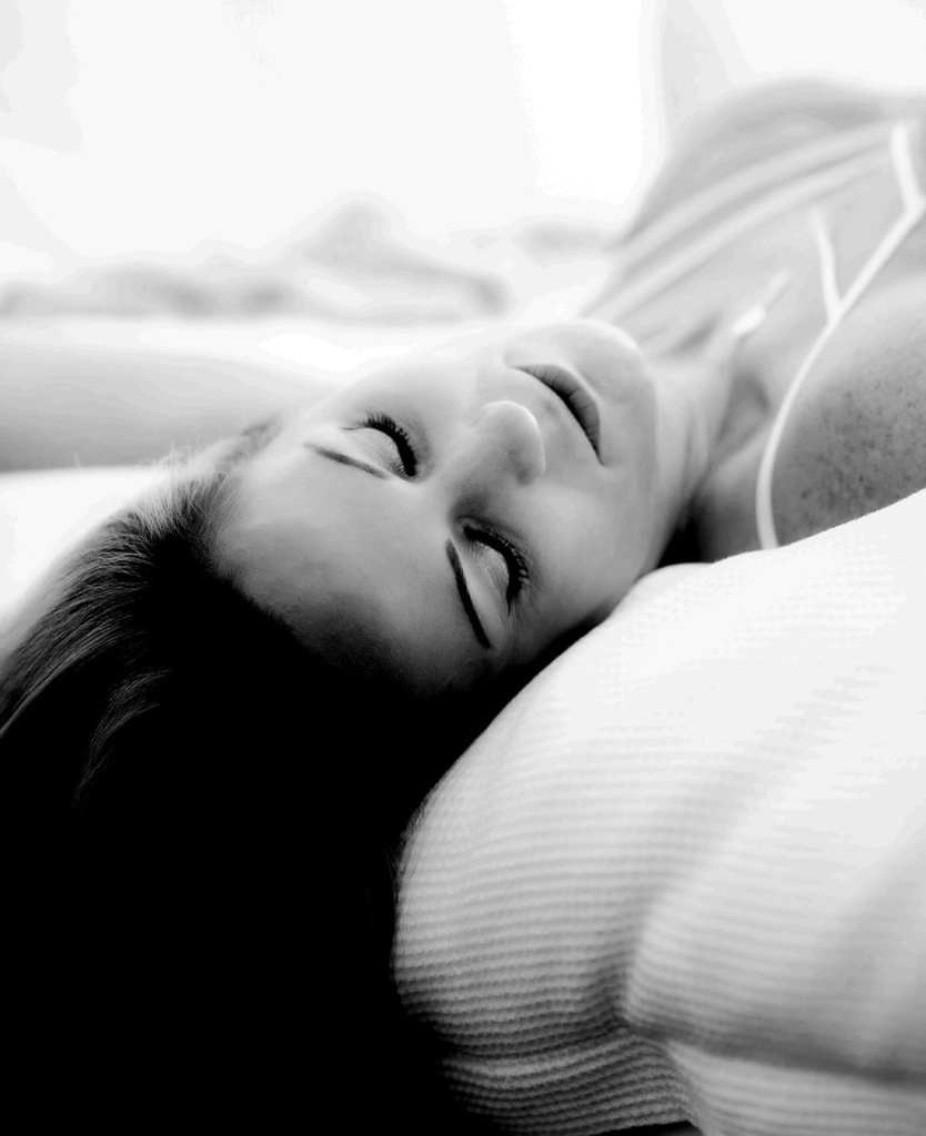 A close up black and white photograph of a woman lying on her back on her bed