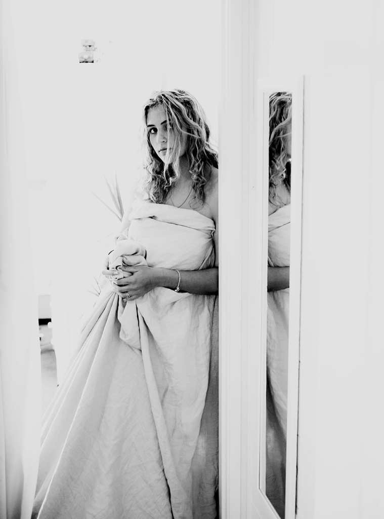 A black and white photograph of a woman with a duvet standing up leaning against a doorway