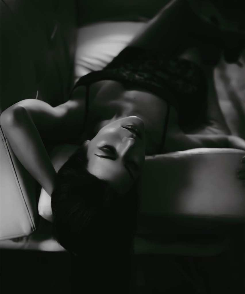 A black and white photograph of a woman with dark hair, lying on her back on a sofa, with her eyes closed
