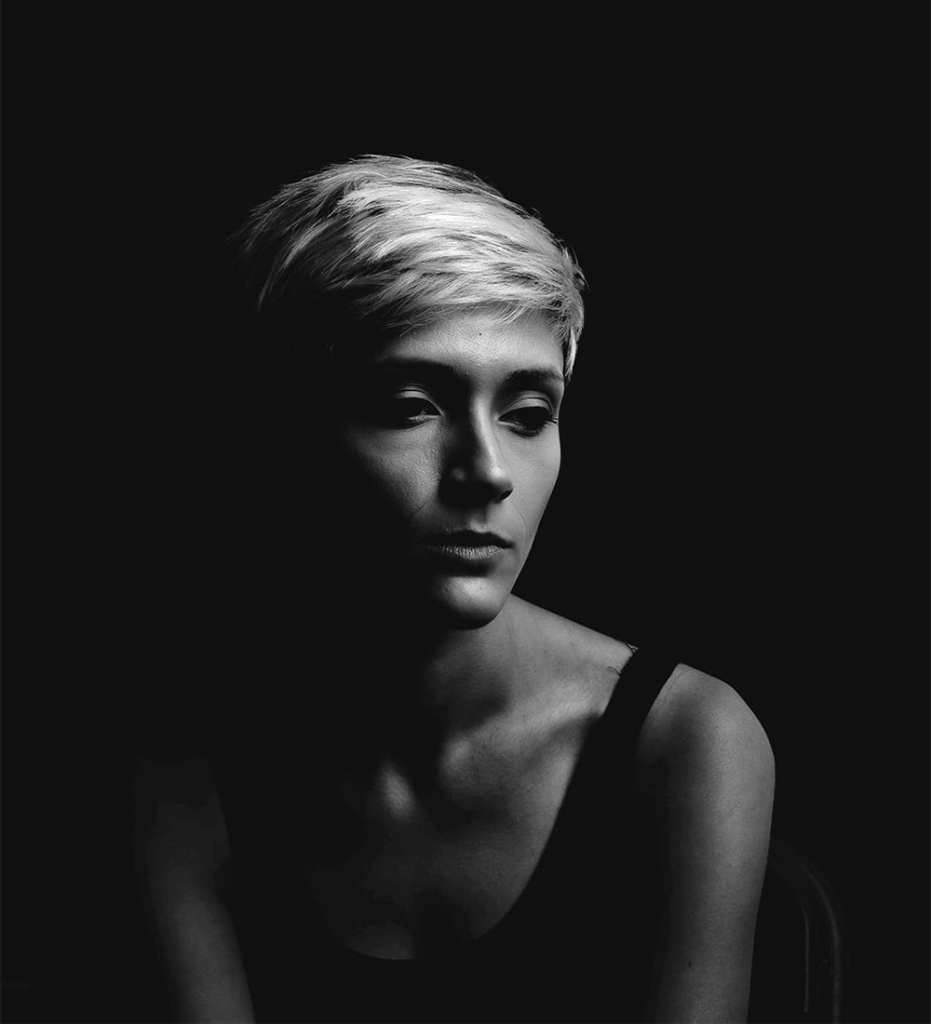 A black and white photograph of a woman with short blonde hair sitting on a chair in darkness