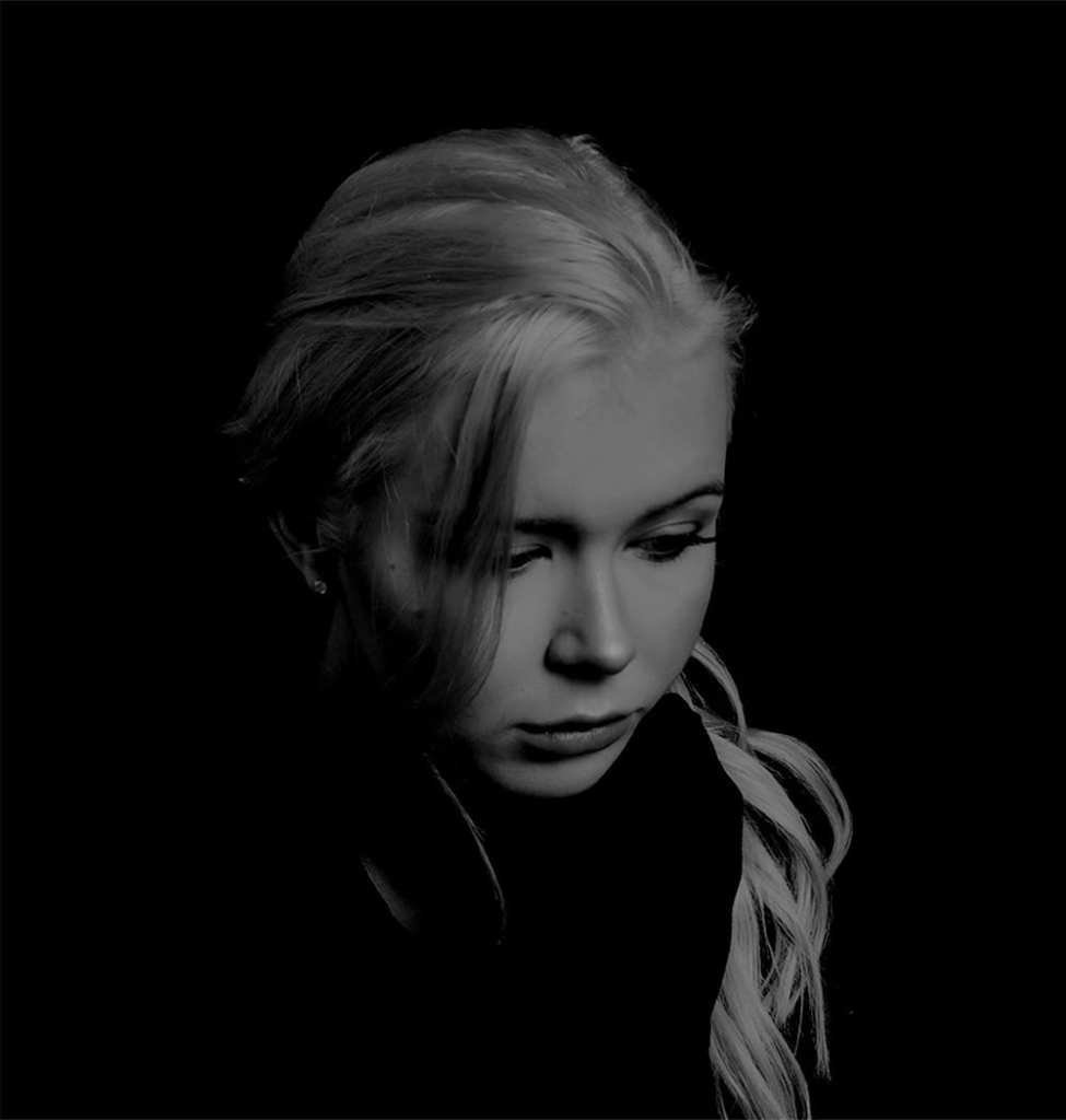 A black and white photograph of a woman with blonde hair, wearing a dark jumper, looking down in a studio space