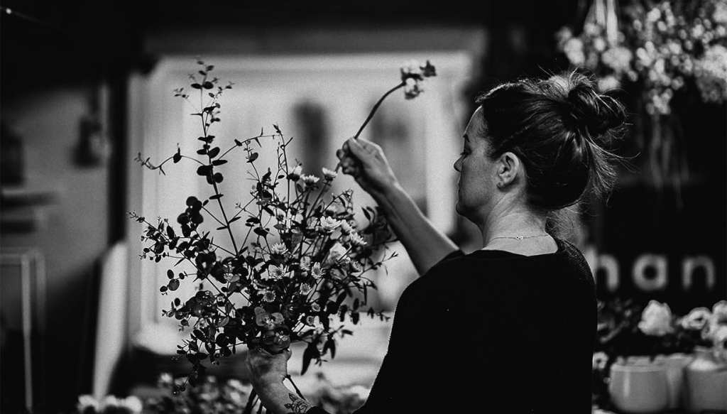 a woman holding a bunch of flowers puts a flower into the bunch