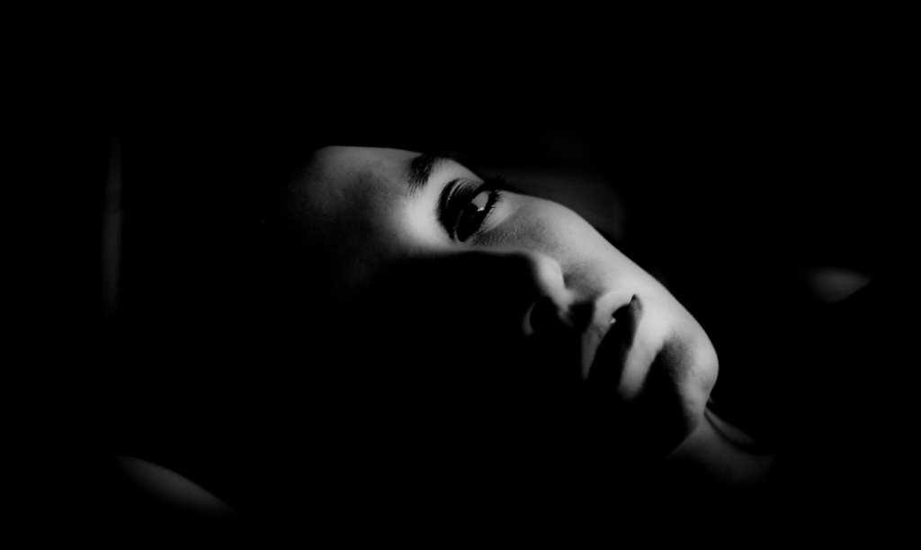 the side of a woman's face with the rest of her in darkness