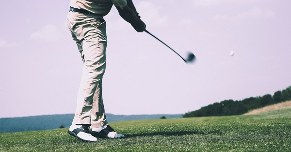 lower body of a golfer swinging a club and hitting a ball off the fairway