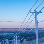 electricity pylon in winter with ice on the pylon and a bright blue background