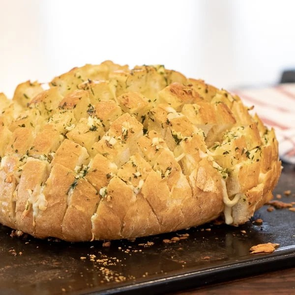 Cheesy pull apart bread made with an artisan rustic round bread loaf, sliced and filled with grated mozzarella cheese, minced garlic, melted butter and parsley. Baked until cheese is bubbly!