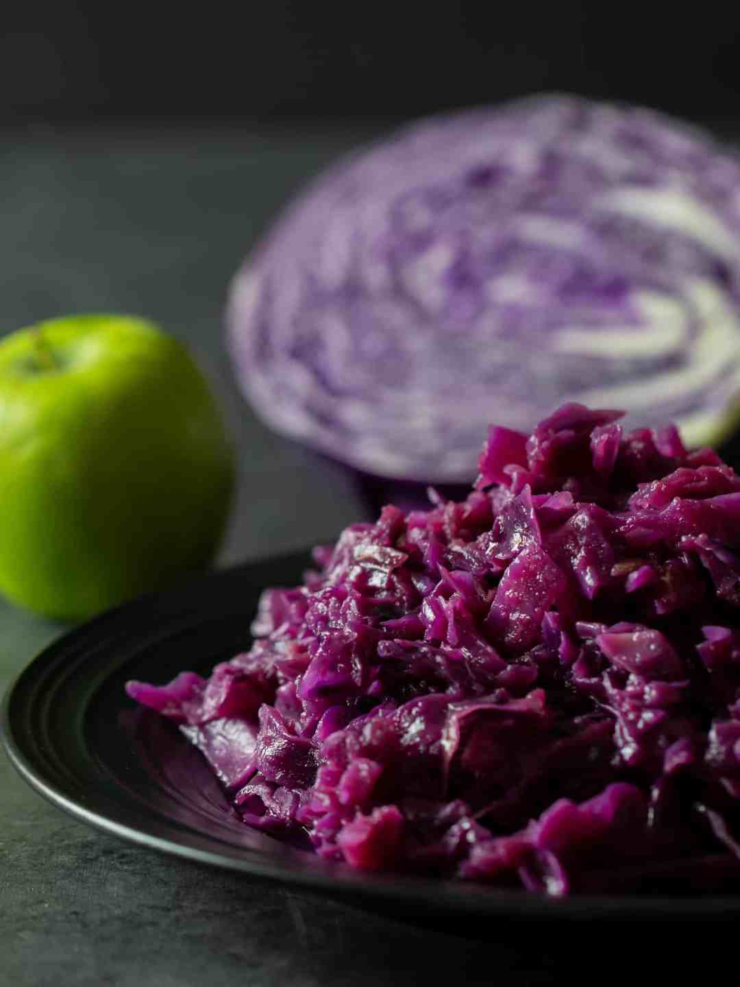 Tall image of a plate of braised red cabbage and apples.