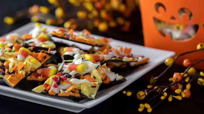 Chocolate bark recipe with a holiday Halloween theme. Sweet dessert treat made with dark chocolate melts, coloured candy melts, candy corn and sprinkles.