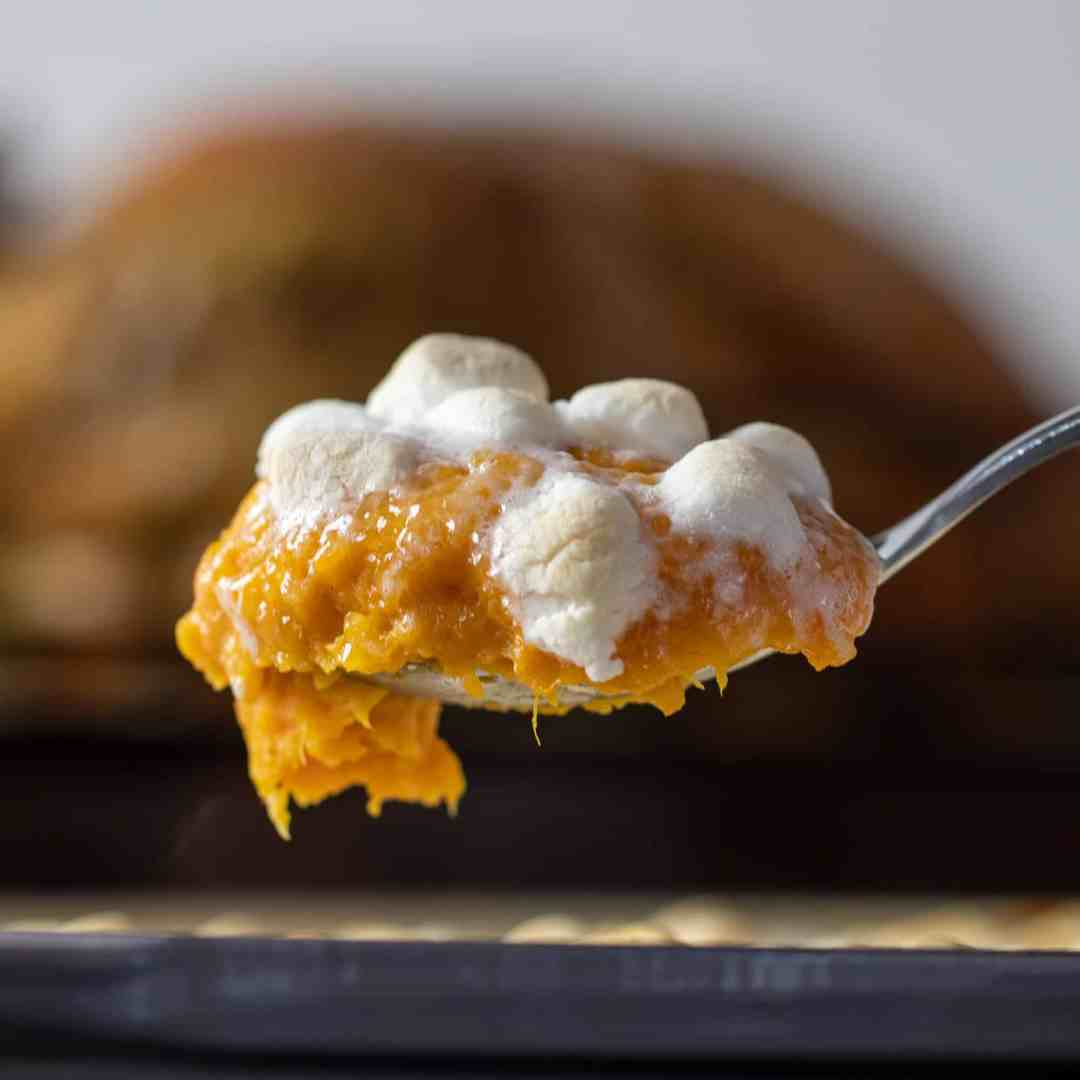Scoop a spoonful of baked sweet potato casserole.