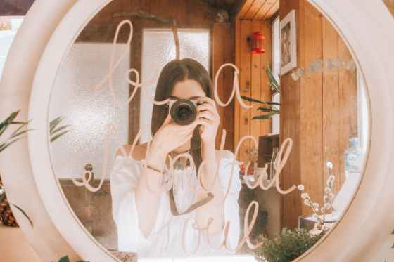 faceless young female taking mirror selfie on photo camera