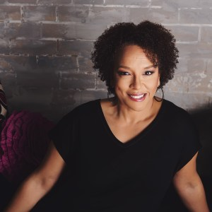 [A lovely Black Womxn sits in front of a gray brick wall. She is wears her natural curls in a way that frames her face. She has a black v-neck blouse on and smiles at the camera.]