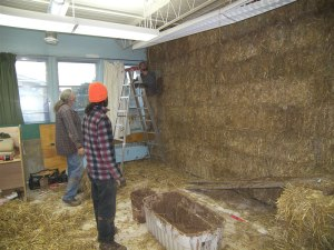 Building a straw bale wall, which will be covered with earth plaster