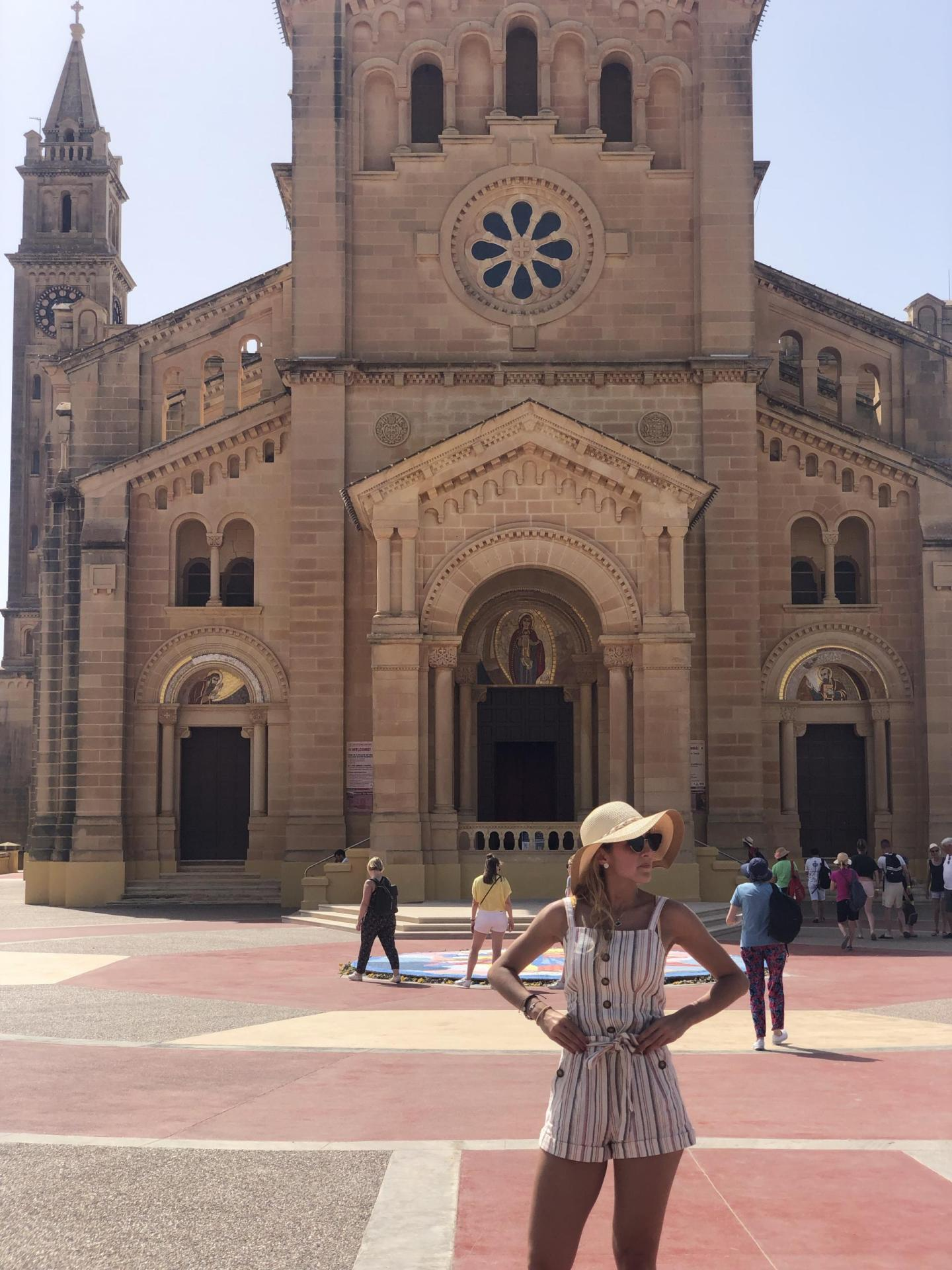 Woman standing in front of a cathedral in Gozo.