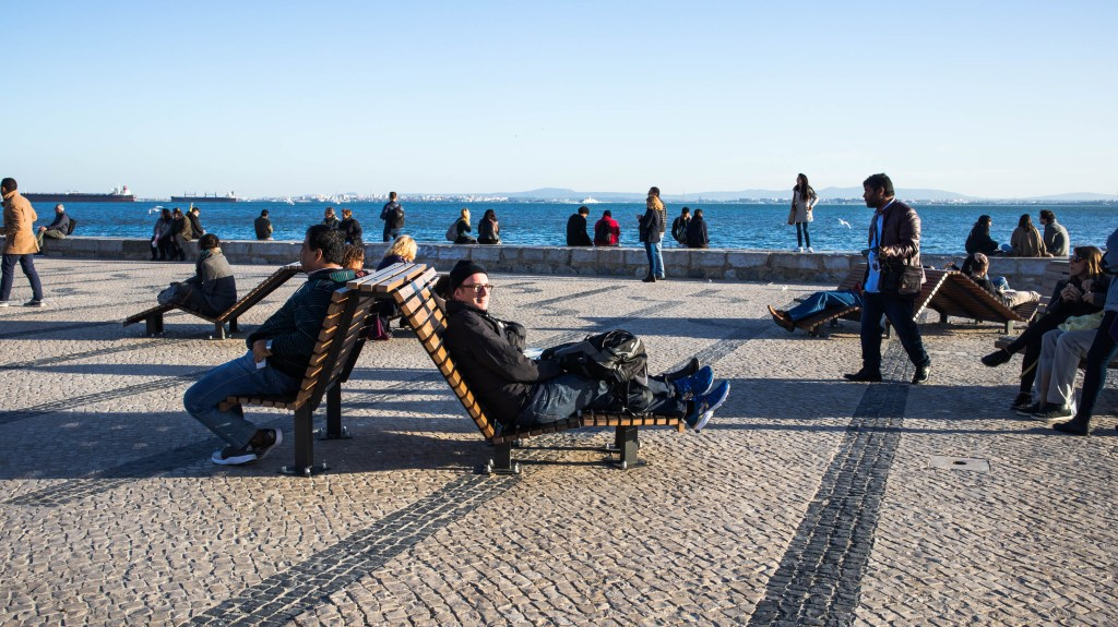people resting on benches on a sunny day by the river in lisbon