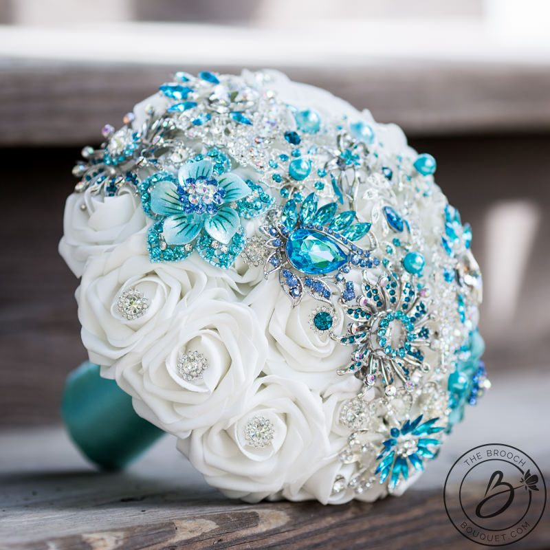 Brooch bouquet with tiffany aqua blue and turquoise strip     The     Turquoise brooch strip bouquet with variety of tiffany  aqua blue  turquoise  and malibu brooches arranged in a strip over white roses