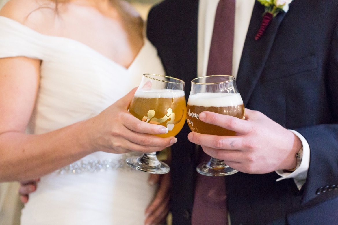 Bride and groom cheering glasses of beer
