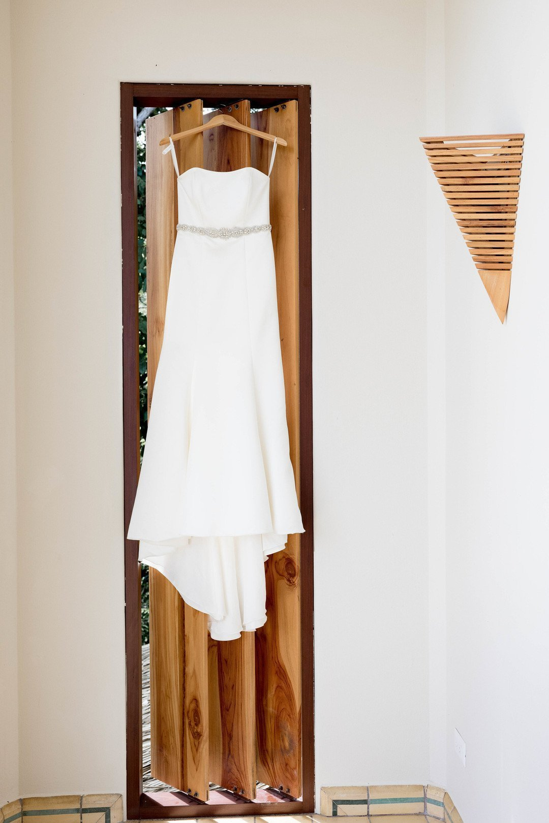 wedding dress hanging on door
