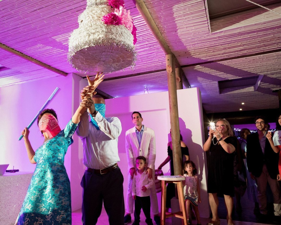 bride and groom hitting pinata at their reception