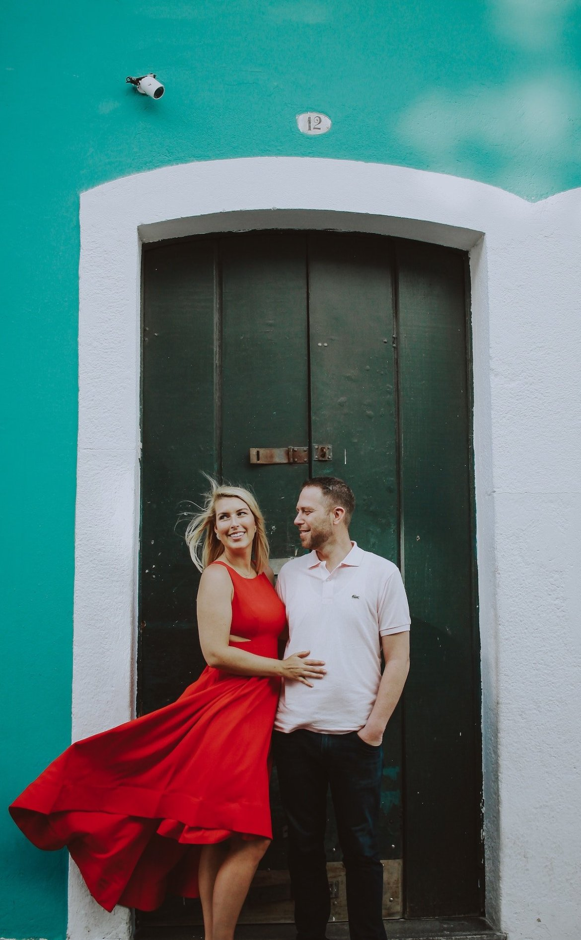Couple posing in front of a colorful wall