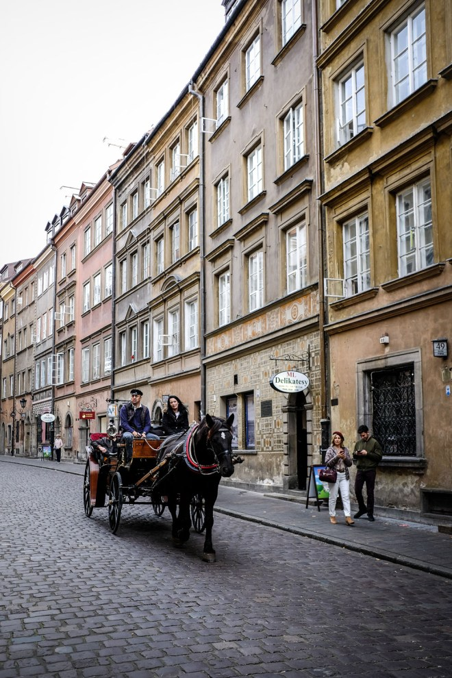 A horse and carriage heading through the streets of Warsaw Old Town