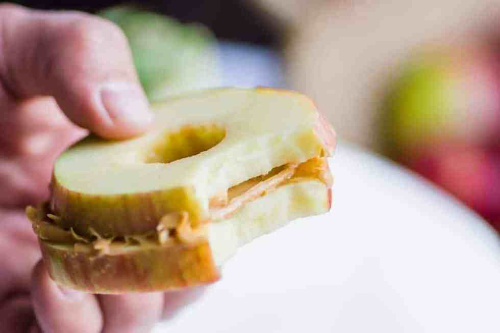 up close shot of apple and peanut butter sandwich with a bite in it