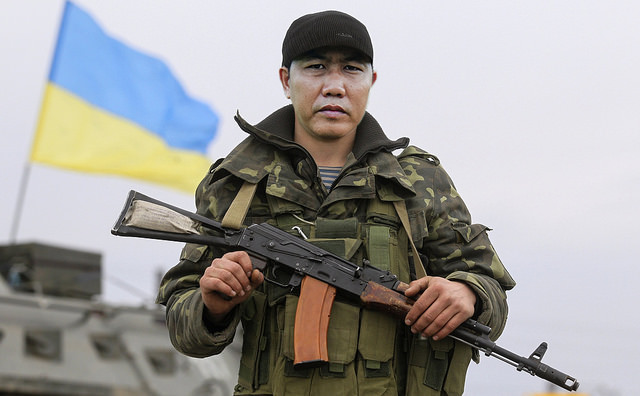 Man holds a Gun in front of a Ukranian Flag