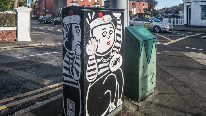 An electrical box by a road, with a mime artist painted on it looking like he's stuck inside