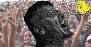 A man screaming with a cheering crowd behind him