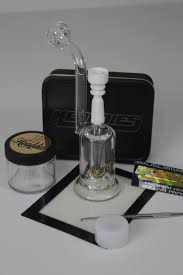 Image of a dab rig which is used to smoke weed out of. The glass dab rig is on a white table.