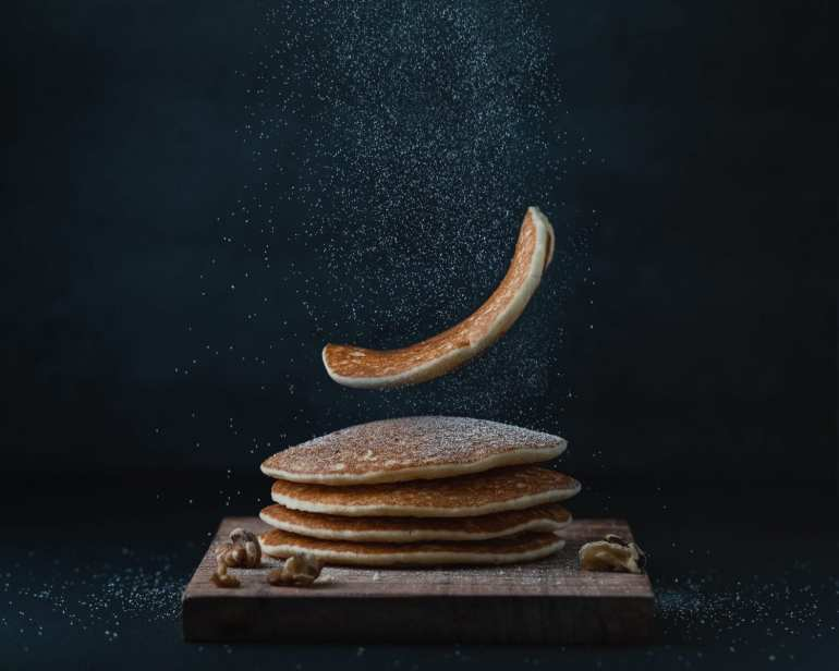 Stack of pancakes with one pancake falling on top of the stack. Black backdrop