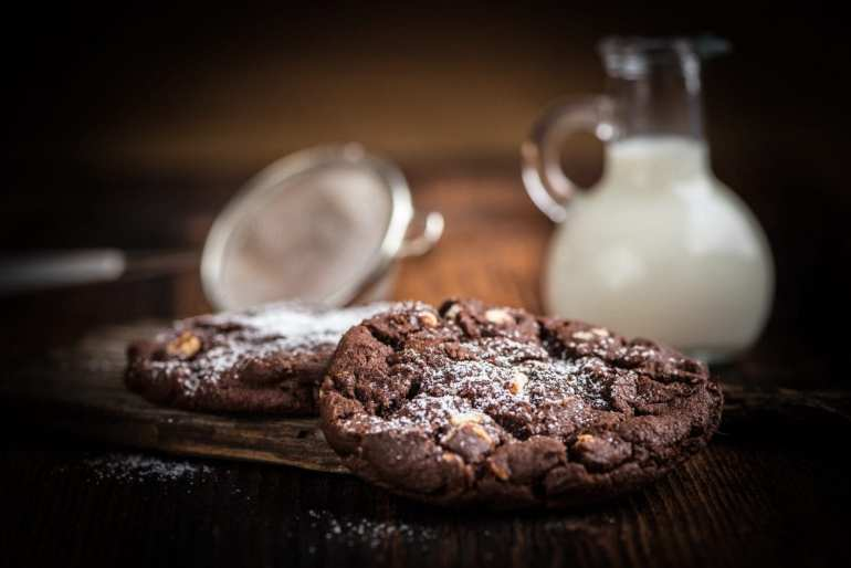Double chocolate chip cookies sitting in front of a glass of white milk.