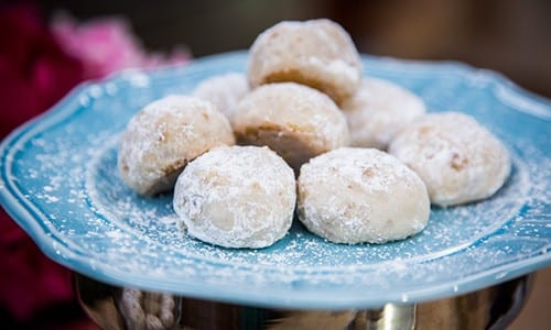 Butterball cookies on a blue plate. The sugar icing is falling off the sides of them.