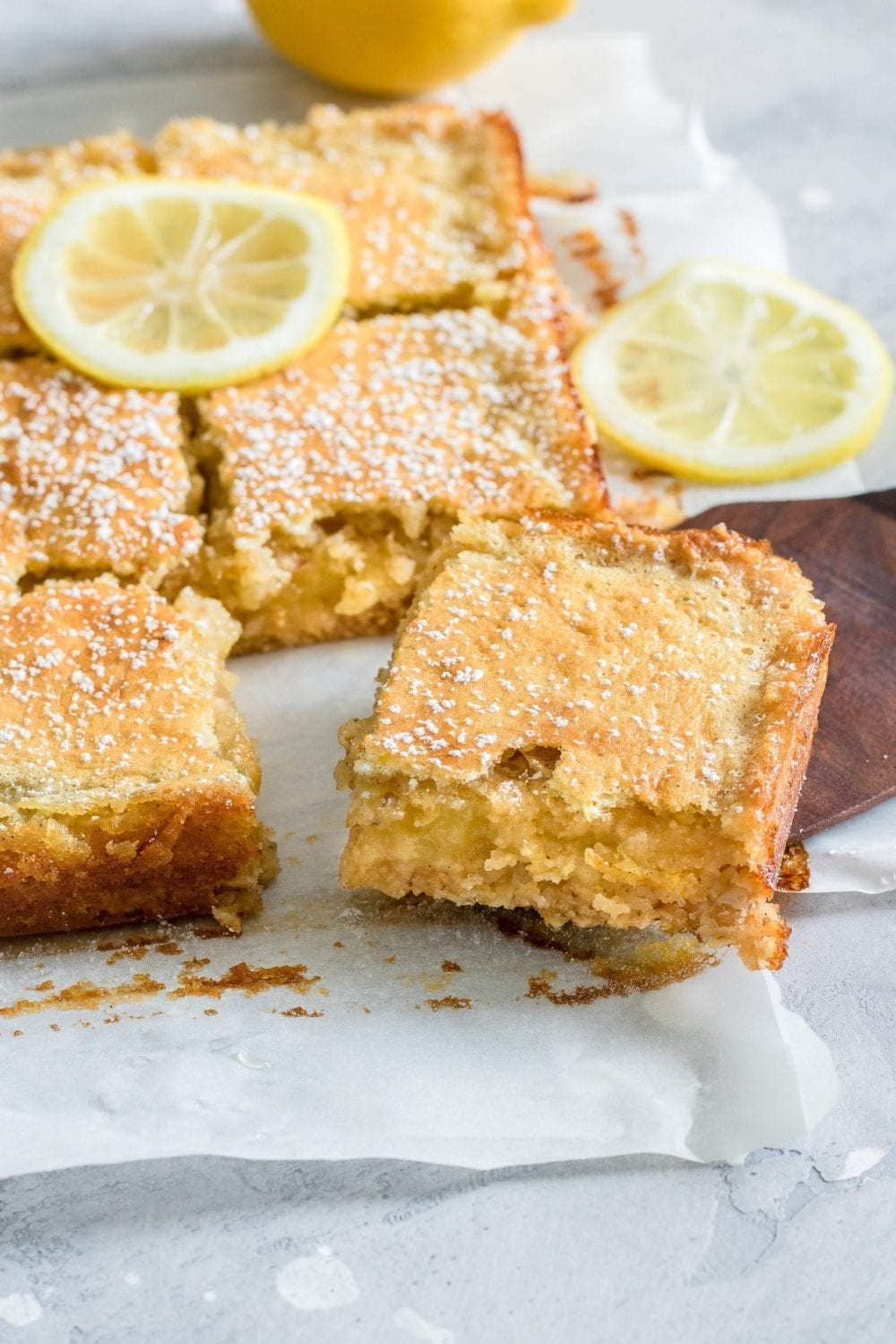 Cannabis infused emon squares with sliced lemons on top of them. The squares are spread on a baking tray