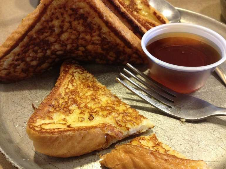 French toast on a grey plate with a fork and spoon. weed maple syrup in a cup on the plate