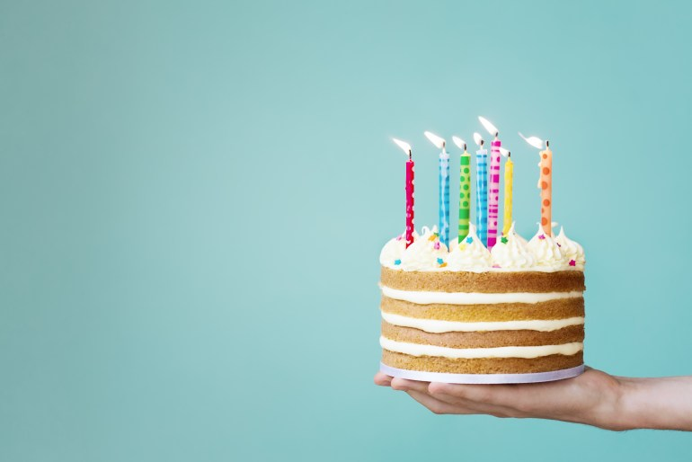 Weed birthday cake with buttercream and colourful candles in a persons hand in front of a blue wall