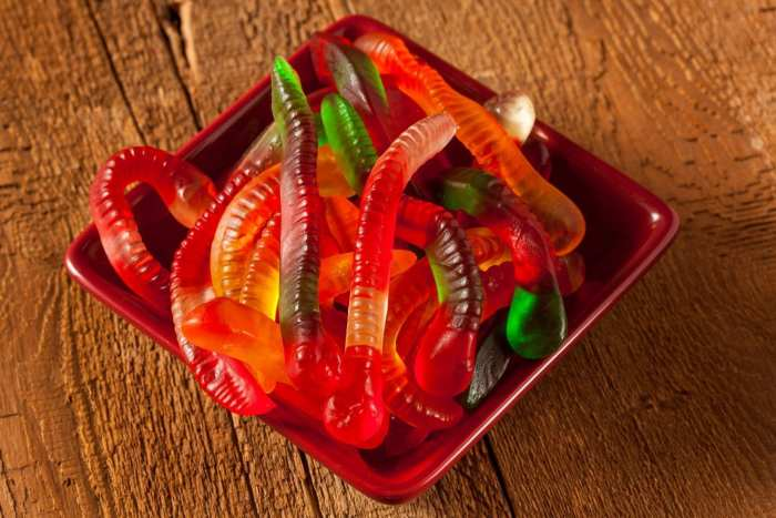 Colourful Fruity cannabis Gummy Worm Candies in a red bowl on a wooden tabe
